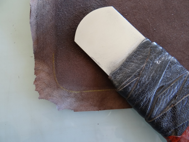 The goatskin is pared and ready to paste. This shows he paring for the rounded portfolio corners