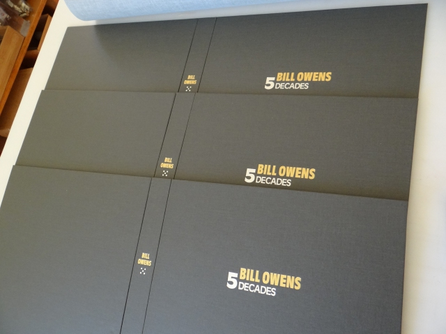 The final 3 Bill Owens 5 Decades boxes stamped with the portfolio tile on the spine and cover