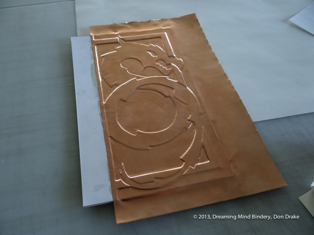 Debossing the copper onto the three dimensional substrate to create a copper journal cover