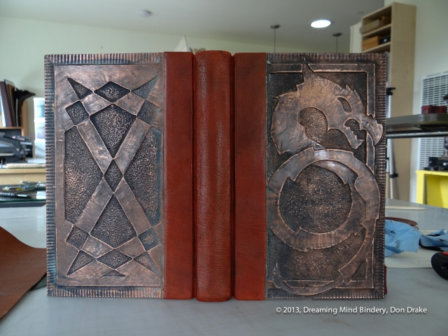 A quarter bound, leather and copper journal with a dragon design on the front cover and a geometric design on the back cover. The copper has a dark, almost black patina created with vinegar and salt.