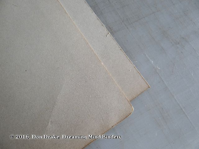 A detail showing two old sheets of paper; one with edges worn with time and use, the other showing freshly cut edges