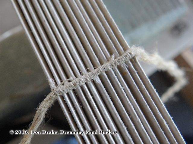 Detail of thread wrapping around a sewing cord