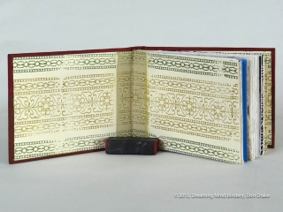 An interior view of Don Drake's binding of the Bay Area Book Artists' (BABA) collaborative project, AlphaBeastiary, showing the block printed endpapers he created for the project.